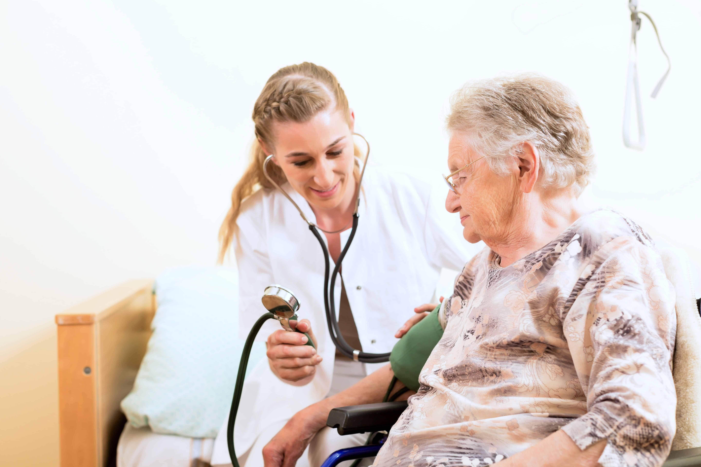 Sygeplejerske behandler ældre kvinde.